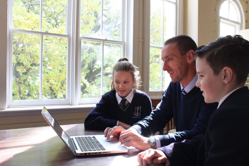 Technology image. Male teacher with two students, all looking at the computer together.